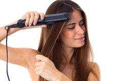 Woman using hair straightener Royalty Free Stock Photos