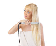 Woman using hair straighteners. Portrait of beautiful woman using hair straighteners over white Stock Photography