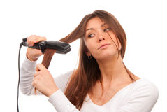 Woman using hair straighteners for hairstyle Royalty Free Stock Photography