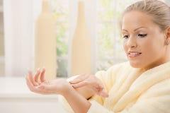 Woman using hand cream Royalty Free Stock Photography