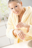 Woman using hand cream Royalty Free Stock Images