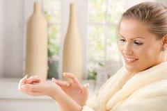 Woman using hand cream. Closeup of young woman wearing bathrobe, using hand cream, smiling Royalty Free Stock Photos
