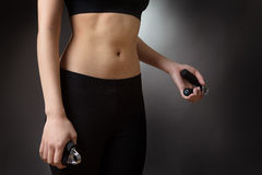 Woman using hand grip. Close up studio shot of a fitness womans abdomen.  using hand grip exercise for strength Stock Image