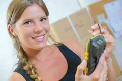 Woman using hand-held inventory device. Woman using a hand-held inventory device Royalty Free Stock Photo