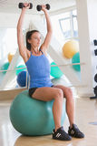 Woman Using Hand Weights On Swiss Ball At Gym Stock Photo