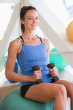 Woman Using Hand Weights On Swiss Ball At Gym Stock Photography