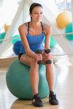 Woman Using Hand Weights On Swiss Ball At Gym Stock Images
