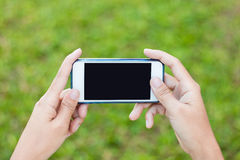 Woman using Hands playing. On a blank screen on modern mobile phone screen Stock Image