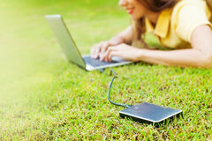 Woman using hard drive disk to backup her data. While lying down Stock Images
