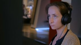 Woman using headphones and listening audio guide at modern jewish history museum. Woman touching interactive display, using headphones and listening audio guide stock video