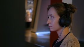 Woman using headphones and listening audio guide at modern jewish history museum. Woman touching interactive display, using headphones and listening audio guide stock video footage