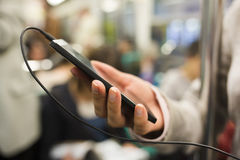 Woman using her cell phone in subway, she listens to music with Stock Image