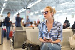 Woman using her cell phone while waiting to board a plane at departure gates at international airport. Stock Photo