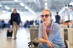 Woman using her cell phone while waiting to board a plane at departure gates at international airport. Stock Photos