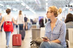 Woman using her cell phone while waiting to board a plane at departure gates at international airport. Casual blond young woman using her cell phone while stock image