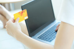 Woman using her credit card on the web lying Stock Photography