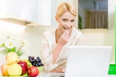 Woman using her laptop computer in the kitchen Stock Photography