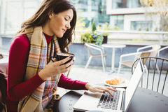 Woman using her laptop and drinking coffee Stock Photography