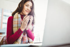 Woman using her laptop and drinking coffee Royalty Free Stock Photo