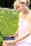 Woman using her laptop on green grass Stock Images