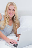 Woman using her laptop on her bed Royalty Free Stock Images