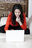Woman using her laptop at home. Attractive woman using her laptop in her living room Royalty Free Stock Image