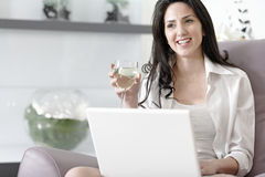 Woman using her laptop at home. Beautiful young woman enjoying a glass of wine in her elegant living room Stock Image