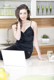 Woman using her laptop in kitchen Royalty Free Stock Photography