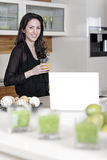 Woman using her laptop in kitchen Stock Images
