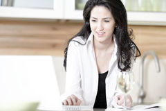 Woman using her laptop in kitchen Royalty Free Stock Images