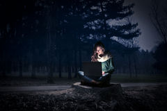 Woman using her laptop at night Stock Image