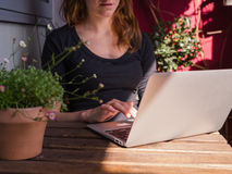 Woman using her laptop outside on balcony Stock Photos