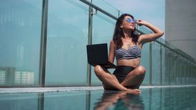 Woman using her laptop in the pool on a sunny day stock footage