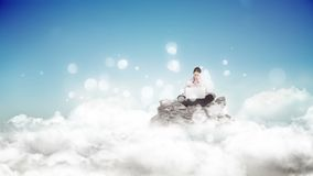 Woman using her laptop surrounded by white bubbles effect. Digital composite of Caucasian woman using her laptop  sitting on a rock surrounded by white bubbles stock footage
