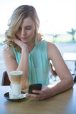 Woman using her mobile phone in the coffee shop Stock Photo