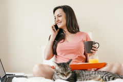 Woman using her mobile phone and having breakfast Stock Photos