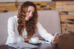 Woman using her mobile phone and holding cup of coffee Royalty Free Stock Image