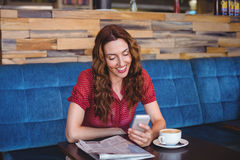 Woman using her mobile phone and holding cup of coffee Stock Photography