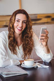 Woman using her mobile phone and holding cup of coffee Royalty Free Stock Images