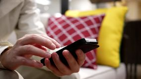 Woman using her mobile phone on sofa stock video footage