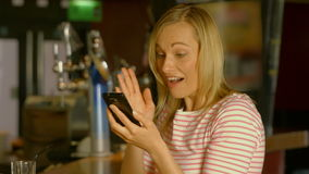 Woman using her phone at the bar. In high quality 4k format stock footage