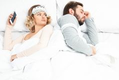 Young woman using smartphone while her husband is sleeping stock images