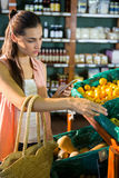 Woman using her phone while buying fruits in organic section Royalty Free Stock Photo