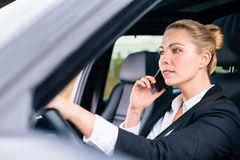 Woman using her phone while driving her car Stock Photos