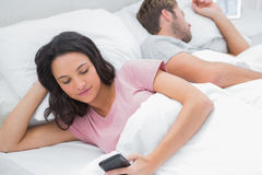 Woman using her phone while her husband is sleeping Stock Images