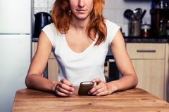Woman using her phone in her kitchen Royalty Free Stock Photography