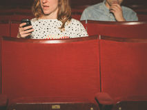 Woman using her phone in theater Royalty Free Stock Image