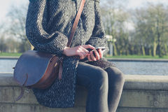 Woman using her phone by water in park Royalty Free Stock Photography