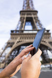 Woman using her Smart phone in front of Eiffel Tower Stock Photography