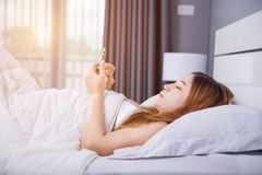 Woman using her smartphone on bed in bedroom with soft light. Woman using her smartphone on bed in the bedroom with soft light Royalty Free Stock Photos